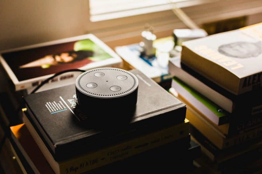 a smart speaker on a pile of books