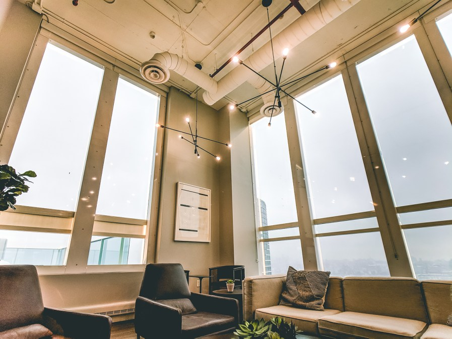 An open-concept corner condo loft with floor length windows and exposed piping in the ceiling