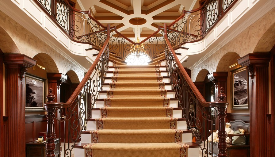 Luxurious staircase with wood rails and cast iron detailing