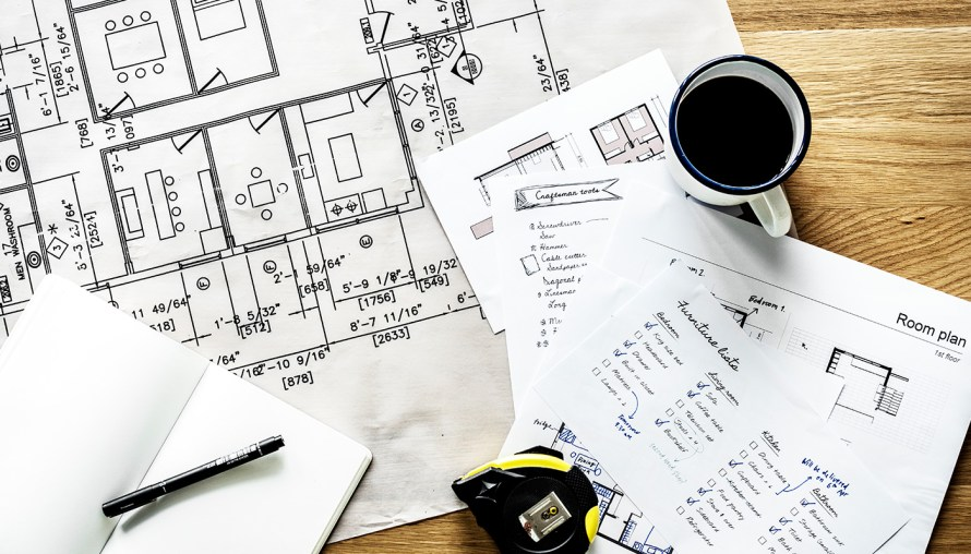Construction plans and blueprints on a desk with notes, coffee and a black marker pen.