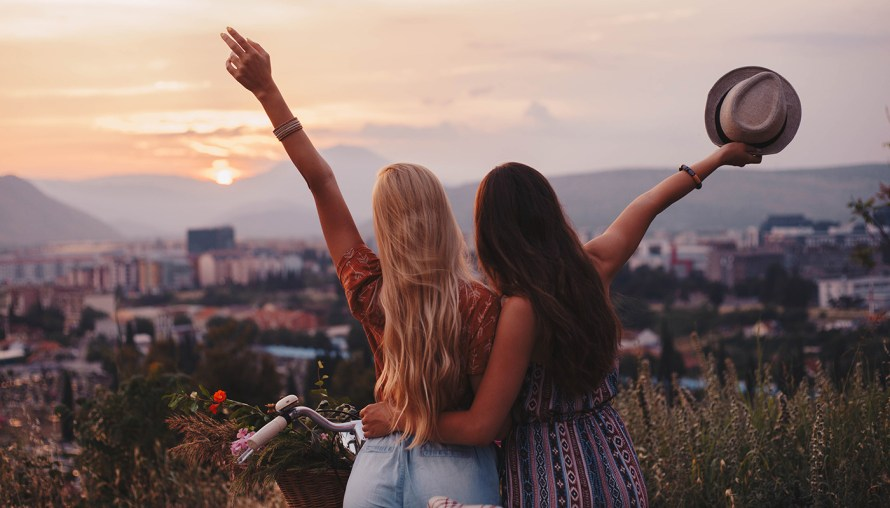 photo of two millennial girls throwing hats off over a hilltop view