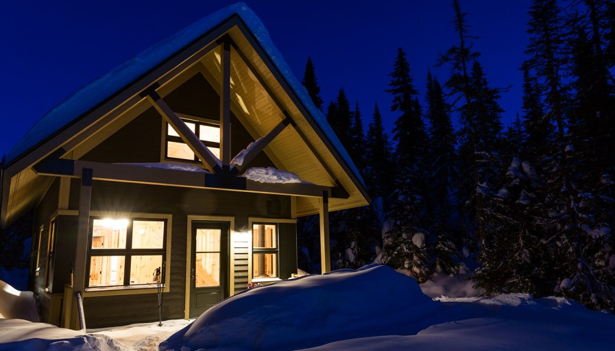 Well-lit log home in winter.