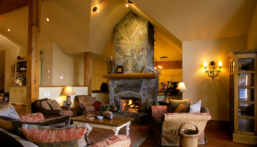 Living room with a large stone fireplace and wood beams.