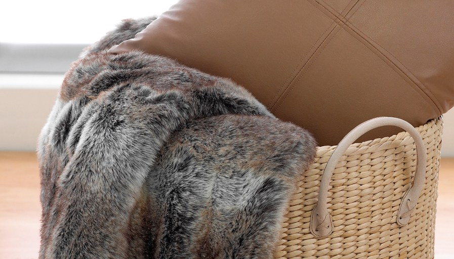 Whicker basket containing fur blanket and leather pillow.
