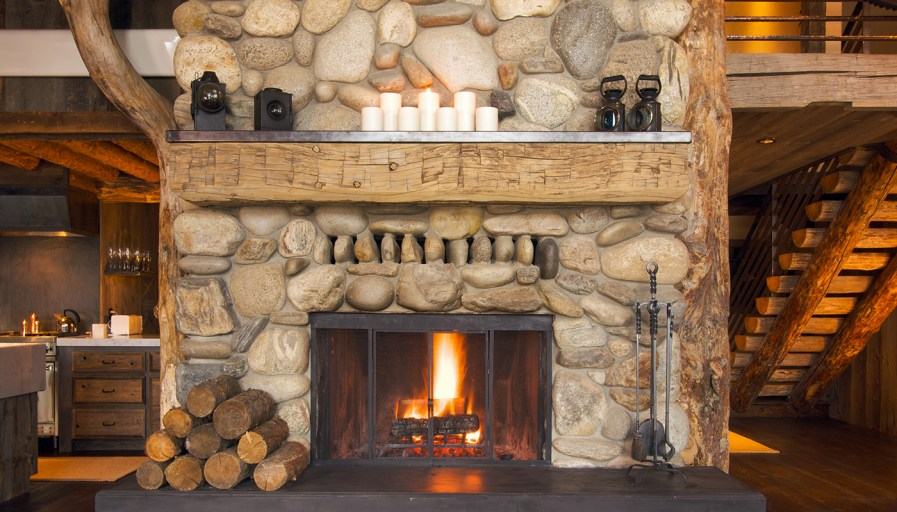 Magnificent stone fireplace with thick slab of wood as mantel.