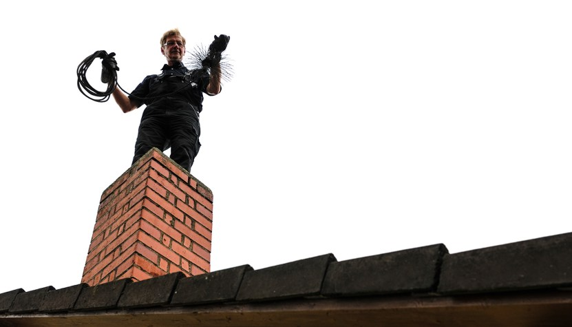 Man standing on roof holding tools to clean a chimney.