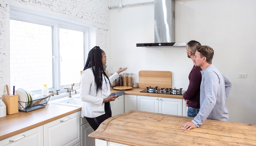A woman gesturing towards the stove in front of two men
