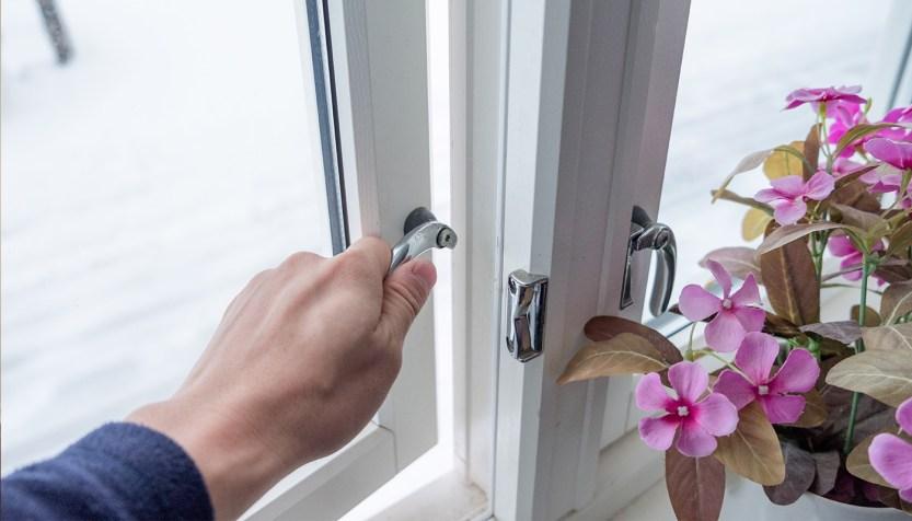 Man opening a window in winter