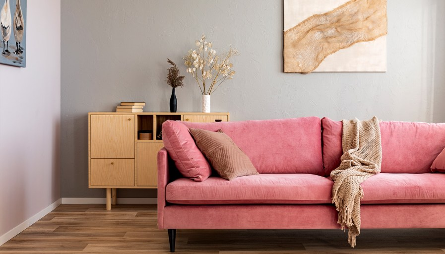 Pink couch filled with beige pillows and a beige blanket