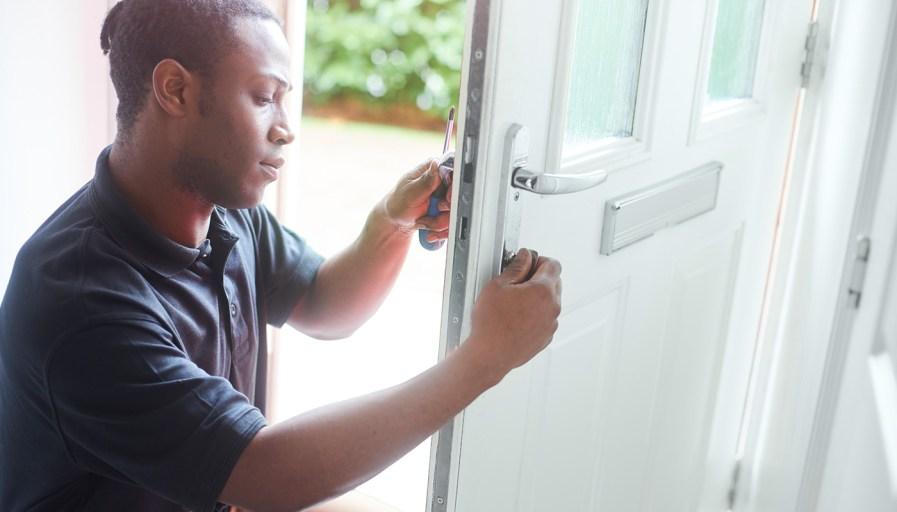 A locksmith changing a door lock.
