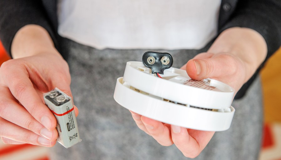 A person replacing the battery in a smoke alarm.