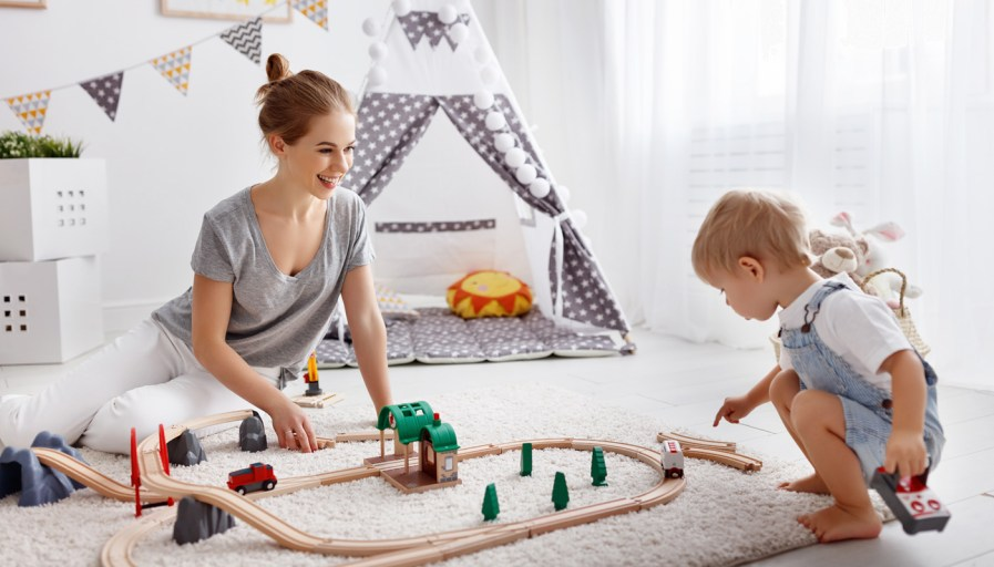 A mom and her child playing with train tacks in a neutral children's playroom.