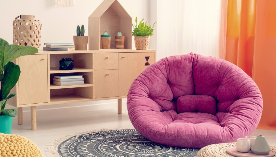 A large cozy pink poof in a neutral play setting with a tea party set.