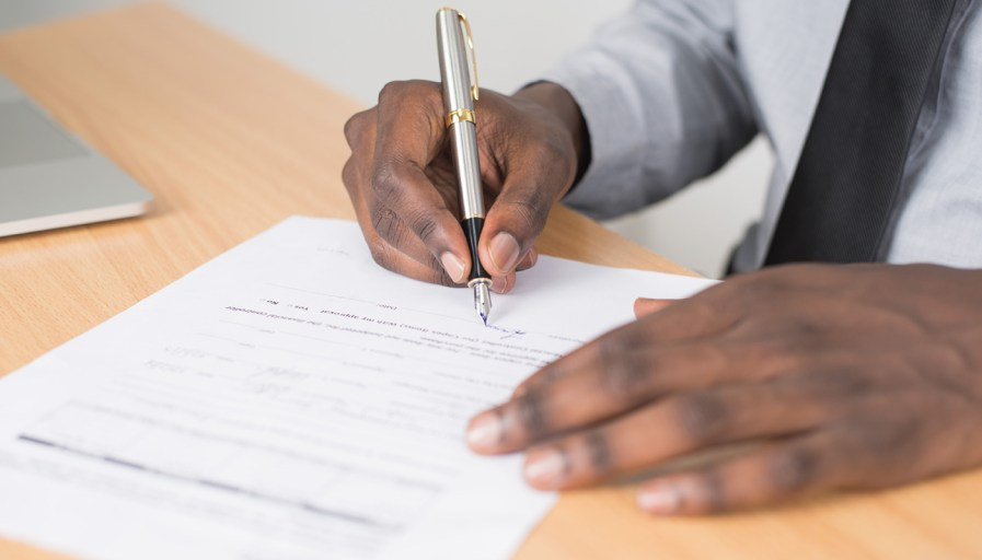 A young adult signing a lease.