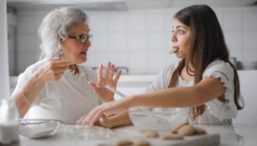 A grandmother and granddaughter talking while having a cookies.