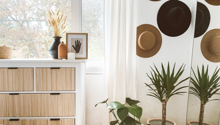 A boho chic room with a DIY dresser, fashionable hats on the wall, surrounded by greenery.