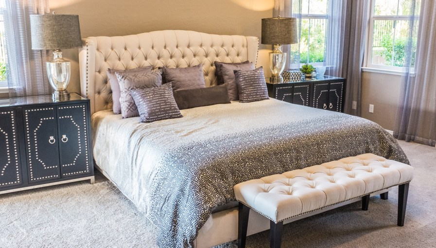 A beautiful bedroom, with a freshly made bed and attention grabbing headboard.