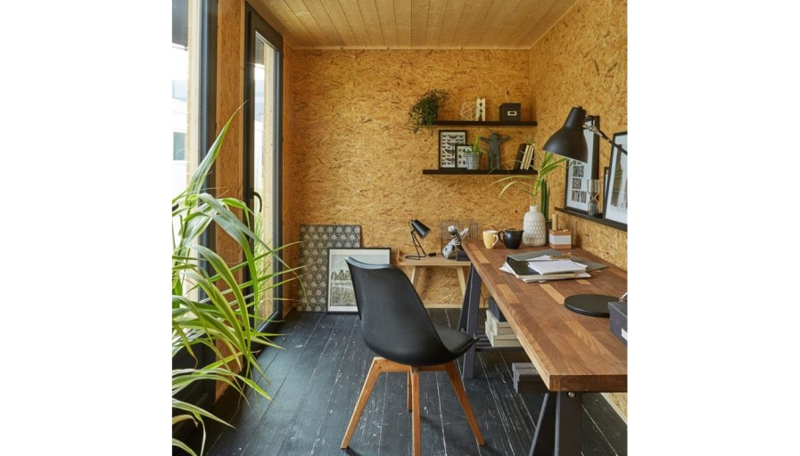 inside a shed that has been converted into a home office with a desk and wooden accents