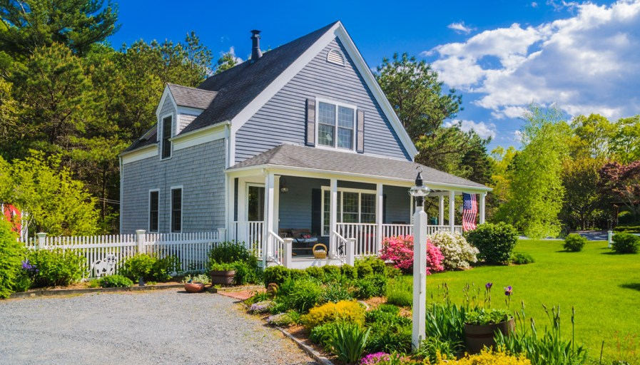 suburban home with a flower garden in the front yard