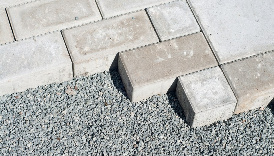 gray interlocking bricks being assembled on gravel