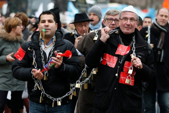 Locks and chains are held by people who participates in the protest march by the heads of small and mid-size French companies in Paris