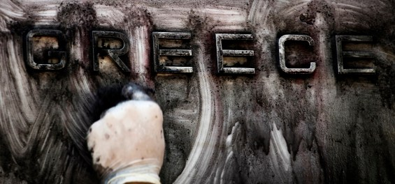 FILE - In this Thursday, Sept. 15, 2011 file photo, a worker cleans the paint-splattered by protesters entrance of the bank of Greece, in central Athens. Wednesday May 6 marks five years since Greece voted in its first bailout deal in the face of violent popular protests that left three dead. The day was followed by years of turmoil in which the country tried to overhaul its economy in the midst of a downturn matched in depth and length only by the Great Depression. (AP Photo/Petros Giannakouris, File)