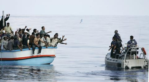 Armed Forces of Malta marines toss bottles of water to a group of around 180 illegal immigrants as a rescue operation gets underway after their vessel ran into engine trouble, some 30km (19 miles) southwest of Malta in this September 25, 2005 file photo. As many as 900 people may have died in Sunday's disaster off the coast of Libya. That would be the highest death toll in recent times among migrants, who are trafficked in the tens of thousands in rickety vessels across the Mediterranean. The mass deaths have caused shock in Europe, where a decision to scale back naval operations last year seems to have increased the risks for migrants without reducing their numbers. The European Union has proposed doubling the size of its Mediterranean search and rescue operations in response to the crisis.  REUTERS/Darrin Zammit Lupi/Files   MALTA OUT. NO COMMERCIAL OR EDITORIAL SALES IN MALTA  TPX IMAGES OF THE DAY  PICTURE 02 OF 28 FOR WIDER IMAGE STORY 'ISLE LANDERS' SEARCH 'DARRIN ISLE' FOR ALL IMAGES