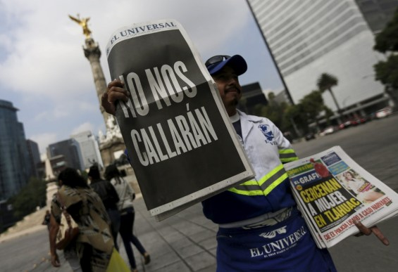 """A street vendor sells copies of Mexico's leading daily El Universal newspaper with a blackened-out front page that reads """"We will not be silenced"""", along a street in Mexico City, August 31, 2015. The page is in reference to the killing of Mexican news photographer Ruben Espinosa and four other people found dead in a middle-class neighborhood of the capital on July 31, 2015. REUTERS/Henry Romero"""