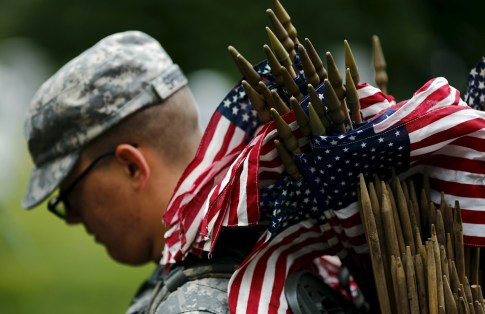 """A member of the Third U.S. Infantry Regiment (The Old Guard) takes part in a """"Flags-In"""" ceremony, ahead of Memorial Day, at Arlington National Cemetery in Washington"""