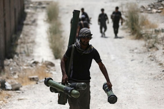 A fighter from the Free Syrian Army's Al Rahman legion carries a weapon as he walks towards his position on the front line against the forces of Syria's President Bashar al-Assad in Jobar, a suburb of Damascus, Syria, in this  July 27, 2015 file photo.  Only four or five U.S.-trained Syrian rebels were still fighting in Syria, a top general told Congress on September 16, 2015, a stark admission of setbacks to a fledgling military program that critics have already pronounced a failure. REUTERS/Bassam Khabieh/Files