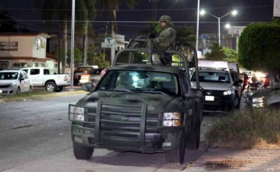"""Soldiers guard the area near a safe house where five people were shot dead during an operation to recapture the world's top drug lord Joaquin """"El Chapo"""" Guzman in Los Mochis"""