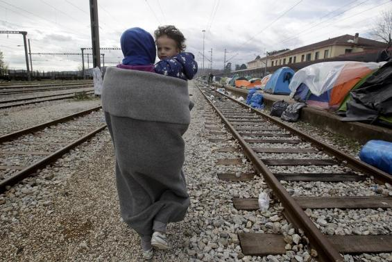 A woman carries her child as they make their way next to railway tracks in a makeshift camp for refugees and migrants at the Greek-Macedonian border near the village of Idomeni