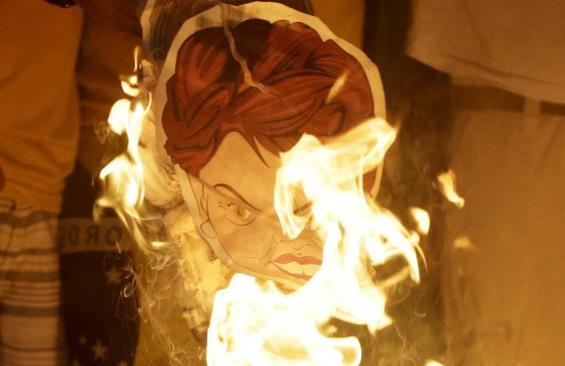 Anti-government demonstrators burn an image of Brazilian President Dilma Rousseff as they celebrate her losing an impeachment vote in the lower house of Congress in Rio de Janeiro