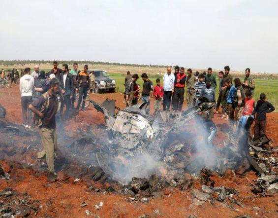 Rebel fighters and civilians gather around the wreckage of a Syrian warplane that was shot down in the Talat al-Iss area, south of Aleppo