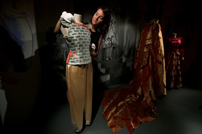 EMBARGOED UNTIL 23:01 GMT SEPTEMBER 15, 2016. A member of staff of the Royal Collection poses with pantomime outfits worn by Britain's Queen Elizabeth and Princess Margaret in the 1943 production of Aladdin, at Windsor Castle in Windsor, Britain September 15, 2016. The exhibition Fashioning a Reign: 90 Years of Style from The Queen's Wardrobe, will show at the castle from September 17, 2016 to January 8, 2017.  REUTERS/Peter Nicholls