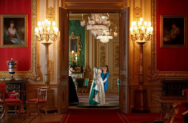 A member of staff of the Royal Collection poses with an evening gown worn by Britain's Queen Elizabeth, at Windsor Castle in Windsor