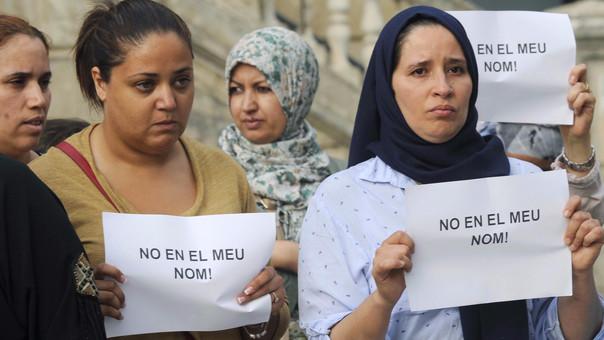 Un grupo de mujeres muestran carteles que dicen 'No en mi nombre' durante el minuto de silencio que la comunidad musulmana ha llevado a cabo en Ripoll.