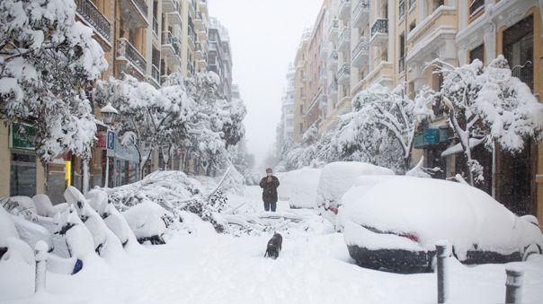 Un hombre toma fotografías mientras pasea a su perro en medio de una fuerte nevada en Madrid.
