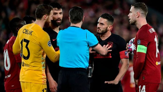 Atletico Madrid players surround referee at Anfield