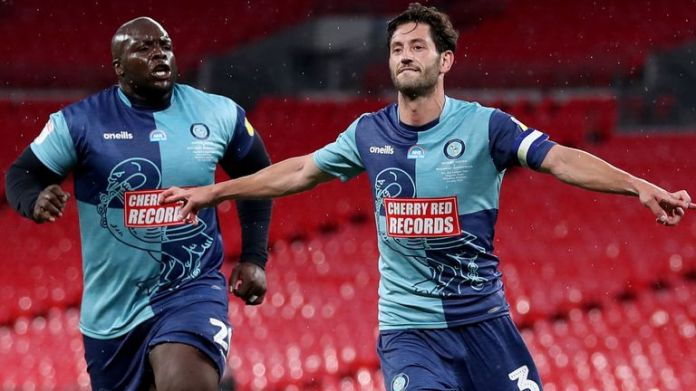 Adebayo Akinfenwa and Joe Jacobson celebrate the latter's sanction against Oxford United