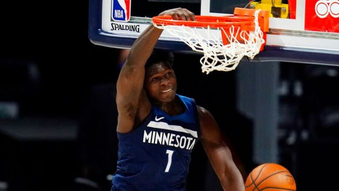 AP - Minnesota Timberwolves guard Anthony Edwards (1) hangs from the rim after dunking the ball for a basket over Denver Nuggets center Nikola Jokic
