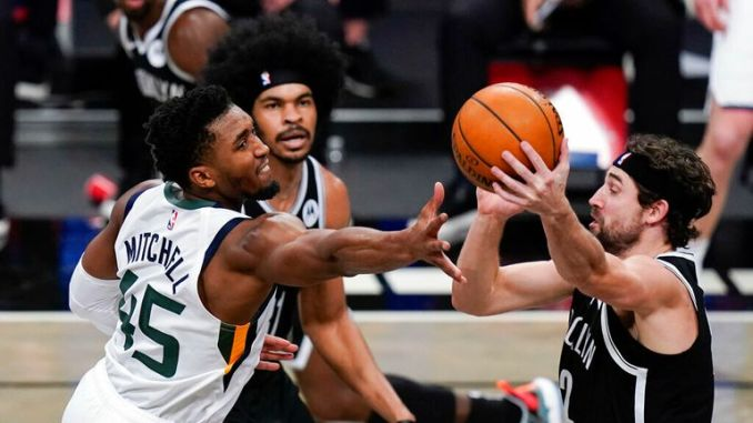 AP - Utah Jazz's Donovan Mitchell (45) fights for control of the ball with Brooklyn Nets' Joe Harris (12)
