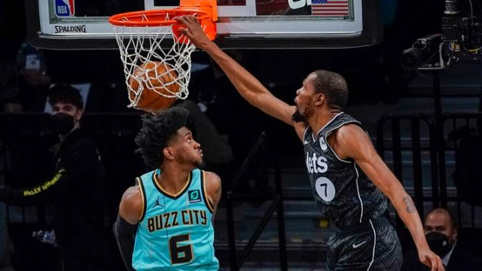 AP - Brooklyn Nets forward Kevin Durant (7) goes to the basket past Charlotte Hornets forward Jalen McDaniels (6)