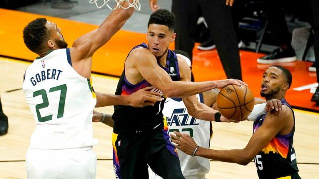 AP - Phoenix Suns guard Devin Booker, right, dishes off around Utah Jazz center Rudy Gobert (27)