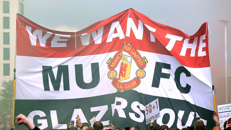 Fans hold up a banner as they protest against the Glazer family, owners of Manchester United, before their Premier League match against Liverpool at Old Trafford, Manchester. Issue date: Sunday May 2, 2021.