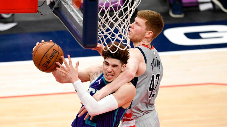 Charlotte Hornets guard LaMelo Ball, left, is fouled by Washington Wizards forward Davis Bertans (42) during the second half of an NBA basketball game, Sunday, May 16, 2021, in Washington. The foul was upgraded to a flagrant one. (AP Photo/Nick Wass)