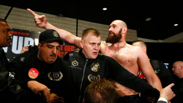 Boxer Tyson Fury, right, exchanges words with opponent Deontay Wilder, after facing each other at a news conference in Los Angeles Wednesday, Nov. 28, 2018, ahead of their heavyweight world championship boxing match on Dec. 1, at Staples Center in Los Angeles. (AP Photo/Damian Dovarganes)