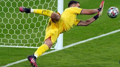 Italy goalkeeper Gianluigi Donnarumma saves from England's Jadon Sancho during the penalty shoot out following the UEFA Euro 2020 Final at Wembley