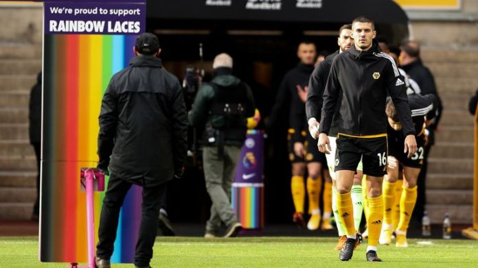 WOLVERHAMPTON, ENGLAND - DECEMBER 12: Conor Coady of Wolverhampton Wanderers leads the team out past Premier League LGBT Rainbow Laces branding during the Premier League match between Wolverhampton Wanderers and Aston Villa at Molineux on December 12, 2020 in Wolverhampton, United Kingdom. The match will be played without fans, behind closed doors as a Covid-19 precaution. (Photo by James Williamson - AMA/Getty Images)
