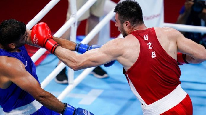 Uzbekistan's Bakhodir Jalolov, right, punches India...s Satish Kumar during their men...s super heavyweight over 91-kg boxing match at the 2020 Summer Olympics, Sunday, Aug. 1, 2021, in Tokyo, Japan. (AP Photo/Frank Franklin II)
